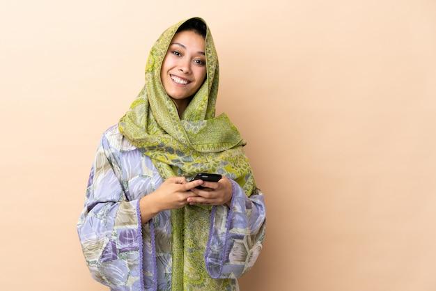 Donna isolata su beige che invia un messaggio con il cellulare