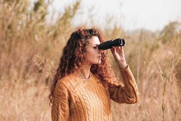 Donna lateralmente che osserva tramite il binocolo