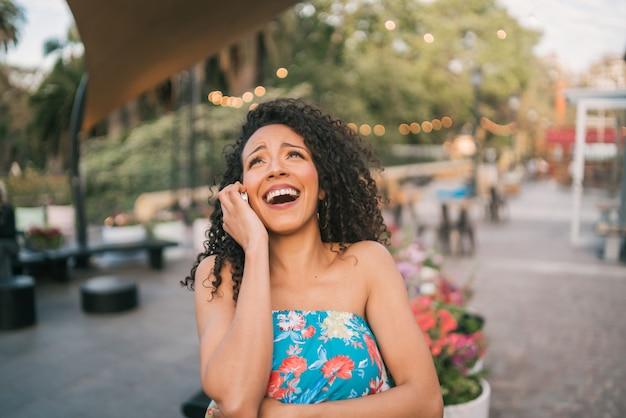 Donna latina afroamericana che parla sul telefono.