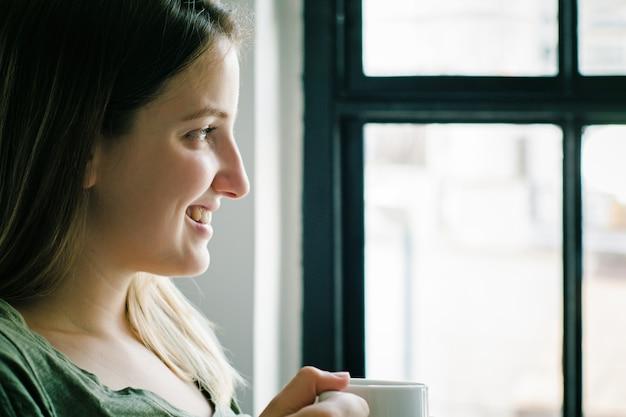 Donna latina che gode della tazza di caffè