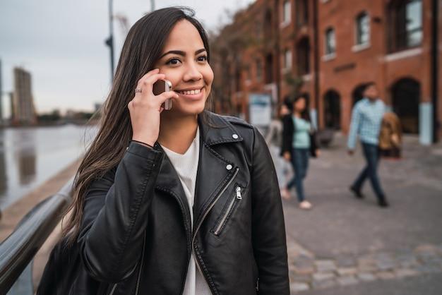 Donna latina che parla al telefono.