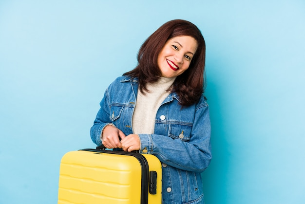 Donna latina del viaggiatore di età di middlr che tiene una valigia isolata ridendo e divertendosi.