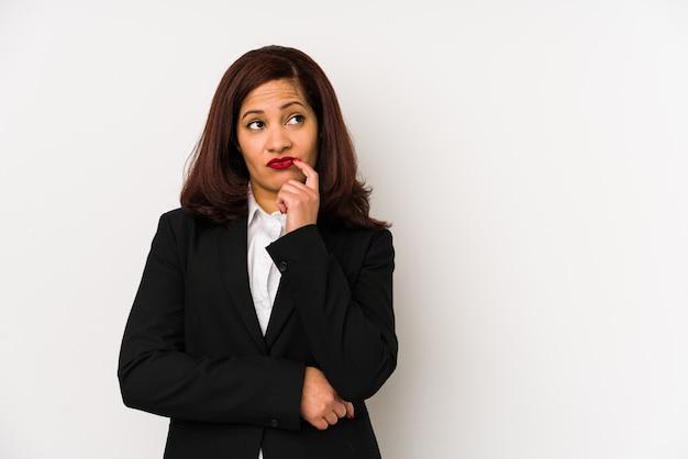 Donna latina di affari di medio evo che guarda lateralmente con l'espressione dubbiosa e scettica.