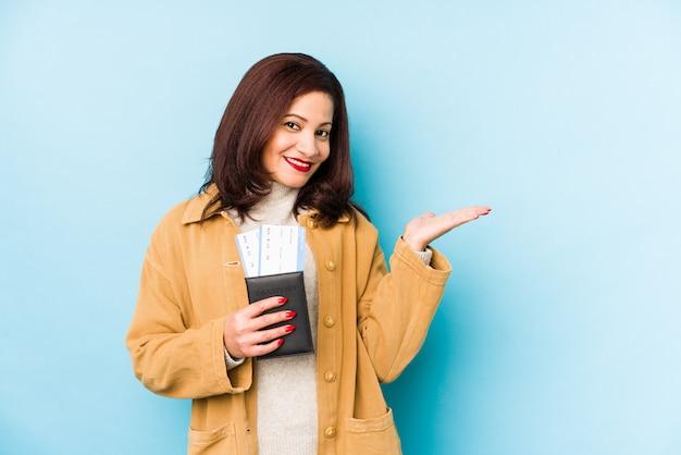 Donna latina di mezza età che tiene un passaporto isolato mostrando uno spazio della copia su una palma e tenendo un'altra mano sulla vita.
