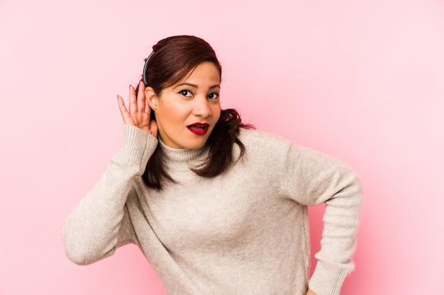 Donna latina di mezza età isolata su una parete rosa che prova ad ascoltare un gossip.