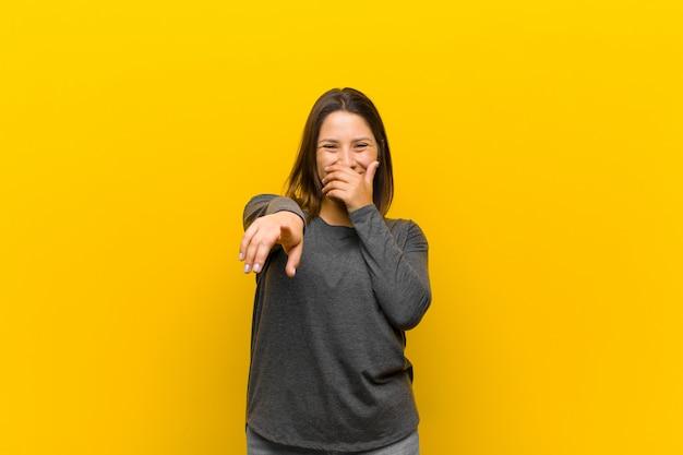 Donna latinoamericana che ride di te, indicando la fotocamera e prendendoti in giro o deridendoti isolato sul muro giallo