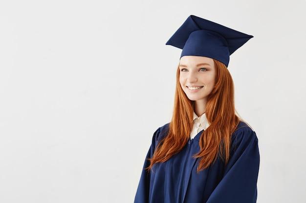 Donna laureata della testarossa felice che sorride sopra la superficie bianca
