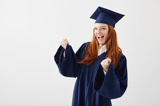 Donna laureata felice nel sorridere di risata di esultanza del mantello.