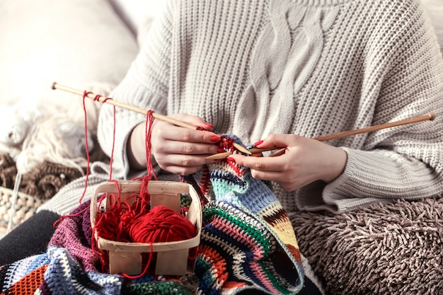 Donna lavora a maglia ferri da maglia sul divano