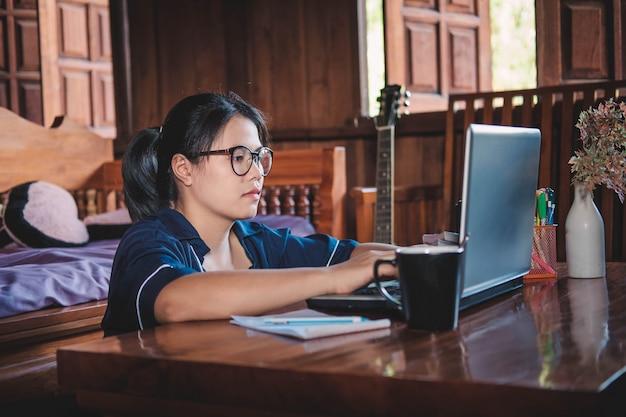 Donna lavoratrice che si siede e che lavora con il computer portatile a casa