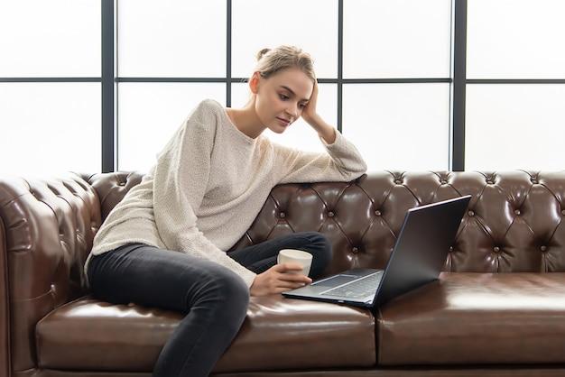 Donna lavoratrice che si siede sul sofà di cuoio