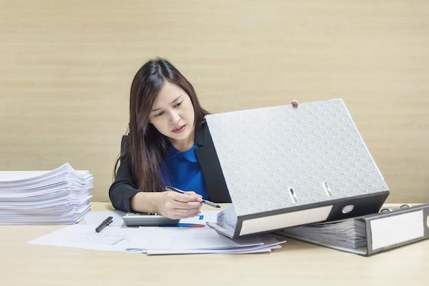 Donna lavoratrice del primo piano che lavora con la carta del lavoro e l'archivio del documento nel concetto del duro lavoro