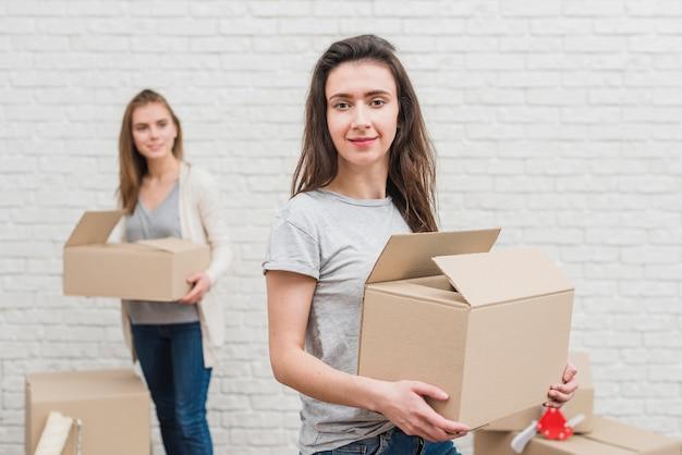 Donna lesbica che tiene la scatola di cartone in movimento e la sua ragazza in piedi a sfondo