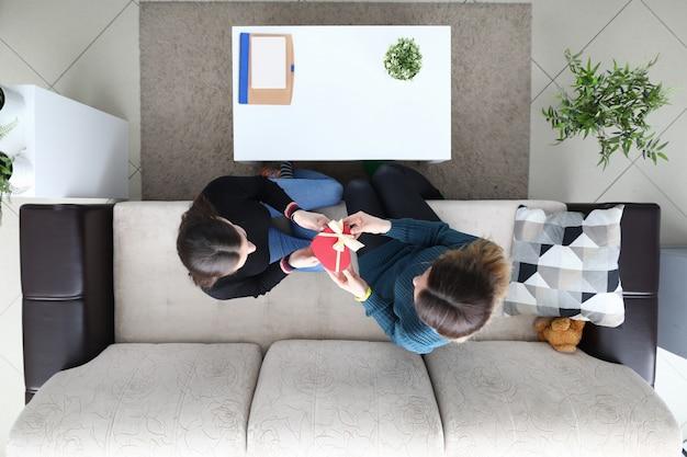 Donna lesbica sedersi al divano e dando regalo vista dall'alto del primo piano