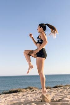 Donna lungo tiro in abiti sportivi a fare jogging in spiaggia