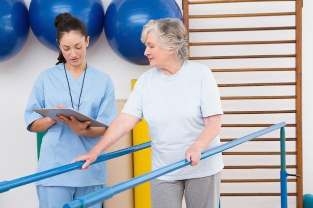 Donna maggiore che cammina con barre parallele con terapeuta
