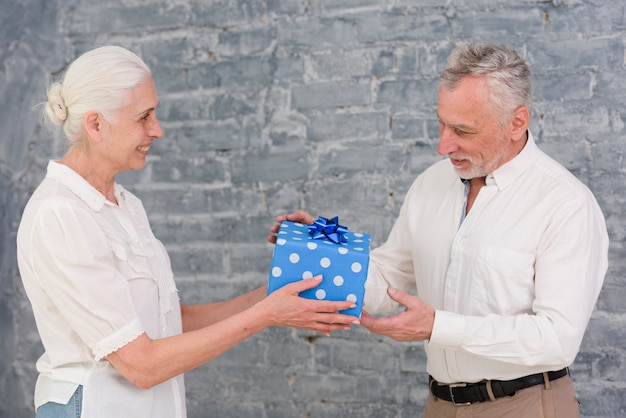 Donna maggiore che dà il regalo di compleanno a suo marito