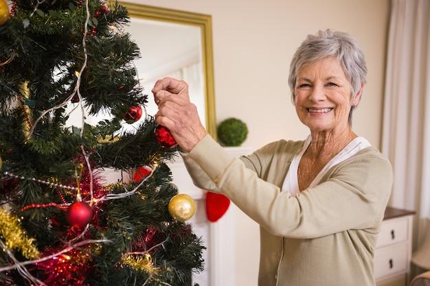 Donna maggiore che decora l'albero di natale