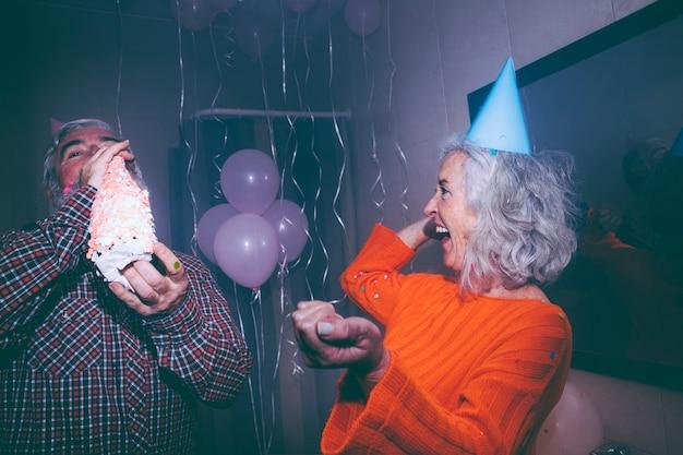 Donna maggiore che esamina suo marito che beve la bottiglia di champagne alla festa di compleanno