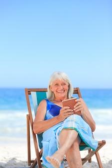 Donna maggiore che legge un libro sulla spiaggia