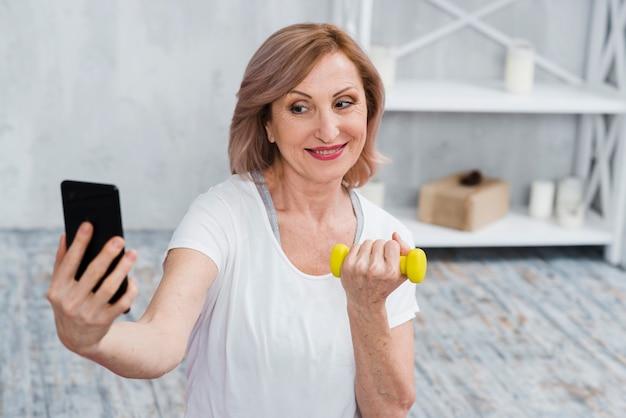 Donna maggiore che prende selfie con i dumbbells a disposizione