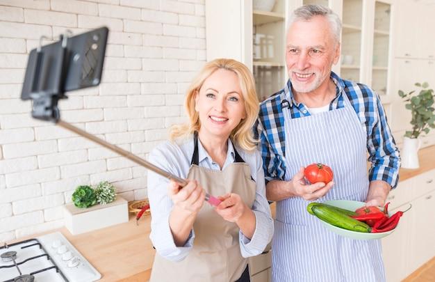 Donna maggiore che prende selfie sul telefono cellulare con suo marito che tiene verdura in mano