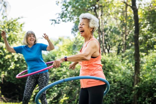 Donna maggiore che si esercita con un hula-hoop