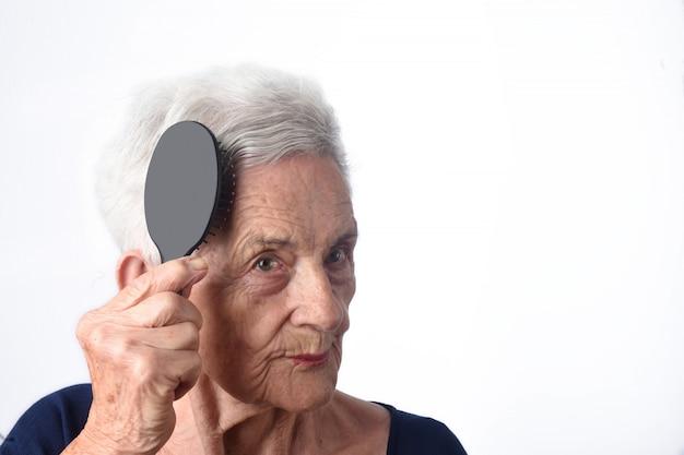 Donna maggiore che si pettina i suoi capelli su priorità bassa bianca