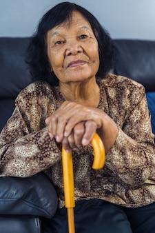 Donna maggiore che sorride con la canna di legno
