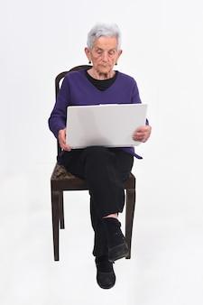 Donna maggiore con il computer portatile su bianco