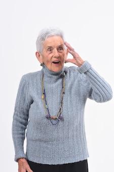 Donna maggiore con l'espressione della dimenticanza o sorpresa su fondo bianco