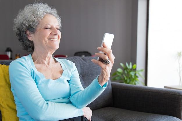Donna maggiore di risata felice che comunica con i nipoti