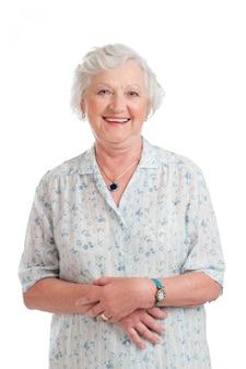 Donna maggiore in pensione sorridente felice isolata su bianco