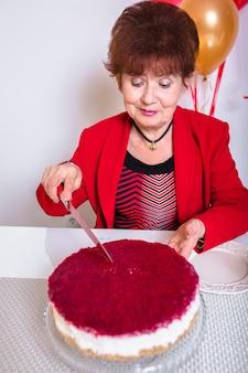 Donna maggiore in vestito rosso che cuting la sua torta della festa di compleanno