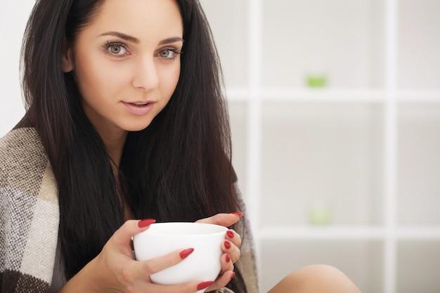 Donna malata a letto, chiamata in malattia, giorno libero dal lavoro tisana bevente vitamine e tè caldo per l'influenza.