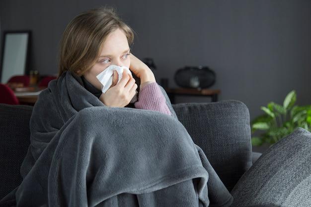 Donna malata annoiata che tiene mano alla testa, soffiando il naso con il tovagliolo