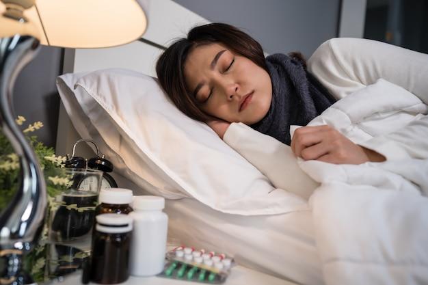 Donna malata che dorme e che sente freddo a letto