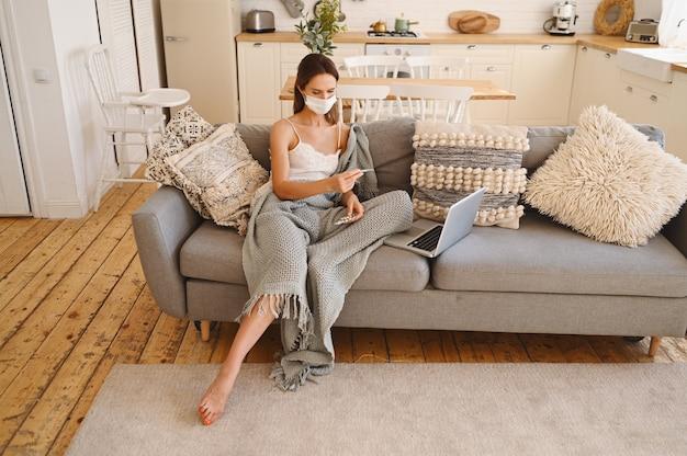 Donna malata che indossa la maschera di protezione del viso, seduto sul divano con il computer portatile e tenendo termometro e pillole durante l'autoisolamento di quarantena domestica.