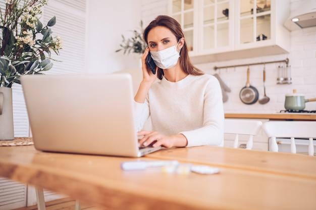 Donna malata che indossa una maschera medica, parlando di smartphone e lavorando su un laptop in cucina a casa durante l'isolamento di quarantena pandemia di covid-19