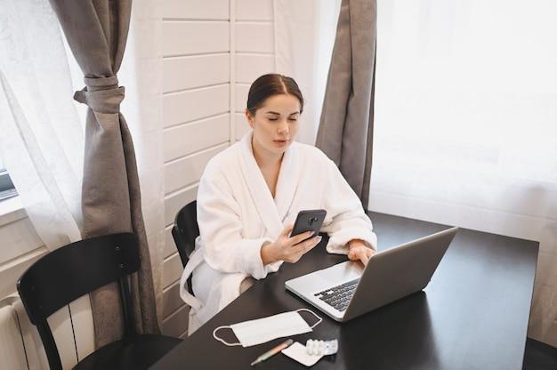 Donna malata che lavora con smartphone e laptop durante l'isolamento di quarantena domestica virus della pandemia di pandemia di covid-19. lavoro a distanza dal concetto di casa. termometro, pillole e una maschera medica sul tavolo