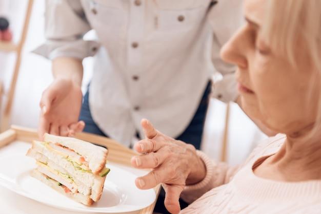 Donna malata che mangia l'uva a letto sandvich.