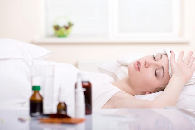 Donna malata che riposa nel letto accanto ai farmaci.