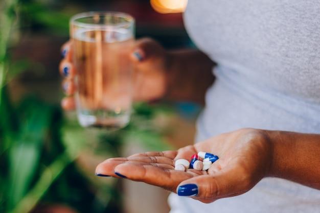 Donna malata che tiene diverse medicine nella sua palma e un bicchiere d'acqua. prendere la medicina. concetto di persona e automedicazione. trattamento sanitario