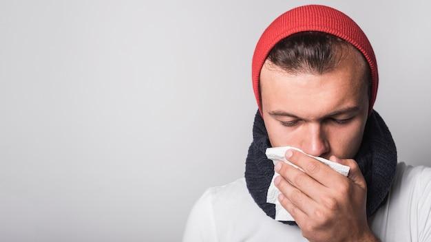 Donna malata che tossisce coprendo la sua bocca contro fondo grigio