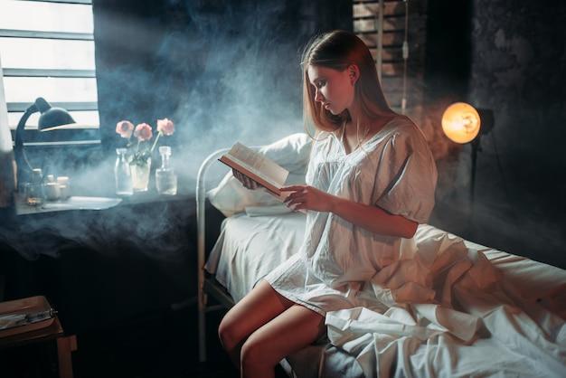 Donna malata con libro seduto sul letto di ospedale