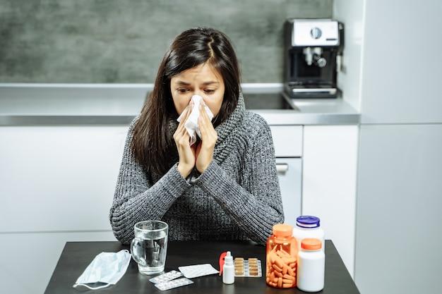 Donna malata con medicina che soffia il naso per pulire carta a casa