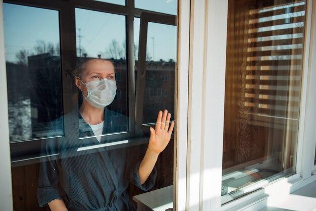 Donna malata in maschera medica guarda fuori dalla finestra durante l'isolamento. trattamento a casa. prevenzione della diffusione del virus. protezione contro l'infezione da coronavirus, pandemie, epidemie e epidemie