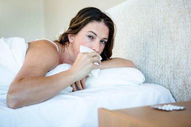 Donna malata sdraiata nel suo letto asciugandosi il naso