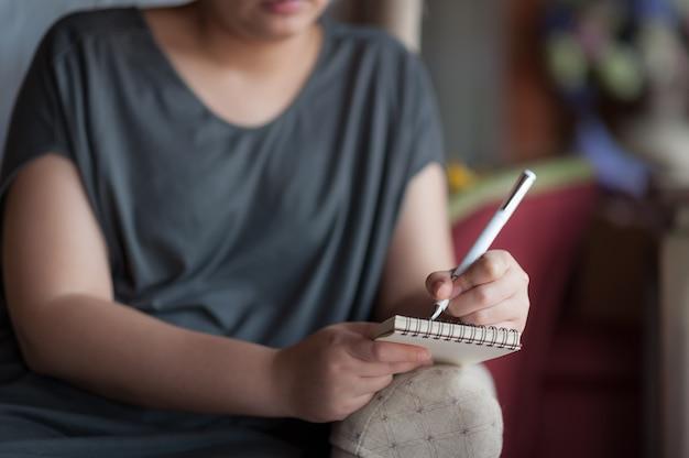 Donna mancina che scrive sul piccolo blocco note