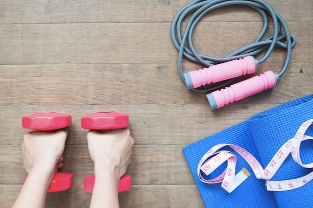 Donna mani che tengono dumbbells con attrezzature sportive e yoga su sfondo di legno, concetto di stile di vita sano